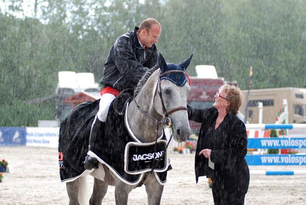 Premiesermoni: I øsende regnvær gratulrer Nina Karstensen fra Bråten Gård Marc Bettinger ra Tyskland med seier i 5-års finalen under Norway Grand Prix - Foto:Avlshest.no